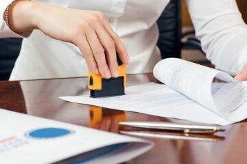 kobieta przybija pieczątkę firmową na dokumentach